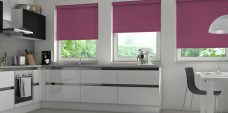 Three Atlantex Aubergine Roller blinds set in kitchen with white cupboards and white accessories