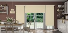 Three Atlantex Beige Solar Reflective Roller blinds set in kitchen with white cupboards,cream accessories and brown walls
