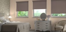 Three Atlantex Brown Solar Reflective Roller blinds set in a bedroom, with white accessories and light peach walls