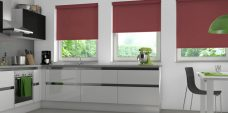 Three Atlantex Cherry Solar Reflective Roller blinds set in kitchen with white cupboards and green accessories