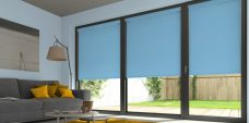 Three Atlantex Blue Roller blinds set in a lounge with light blue walls