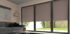 Three Atlantex Brown Roller blinds set in a lounge with peach walls
