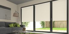 Three Atlantex Cream Roller blinds set in a lounge with cream walls