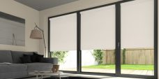 Three Atlantex Dark Beige Roller blinds set in a lounge with light cream walls