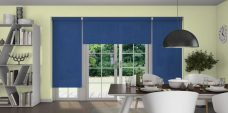 Three Atlantex Dark Blue Roller blinds set in a dining room with light yellow walls