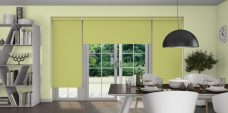 Three Atlantex Fresh Apple Roller blinds set in a dining room with light green walls