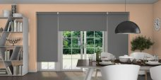Three Atlantex Grey Roller blinds set in a dining room with peach walls