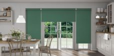 Three Atlantex Hunter Green Roller blinds set in kitchen with white cupboards and white accessories