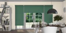 Three Atlantex Hunter Green Roller blinds set in a dining room with off white walls