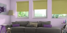 Three Atlantex Lime Solar Reflective Roller blinds set in a lounge with lilac walls
