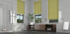 Three Atlantex Lime Roller blinds set in a bathroom with white accessories and grey walls