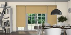 Three Atlantex Muted Gold Roller blinds set in a dining room with off white walls