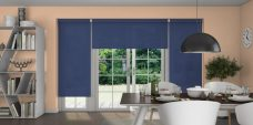 Three Atlantex Navy Roller blinds set in a dining room with peach walls