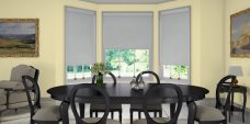 Three Atlantex Silver Roller blinds set in a dining room with light yellow walls