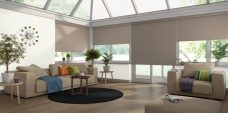 Four Atlantex Taupe Solar Reflective Roller blinds set in a conservatory with neutral colour scheme