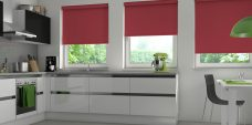 Three Banlight Cerise Roller Blinds set in a kitchen