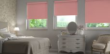Three Banlight Coral Roller Blinds set in a bedroom