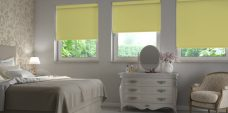 Three Banlight Fresh Apple Roller Blinds set in a bedroom