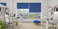 Three Banlight Glacier Blue Roller Blinds set in a living room