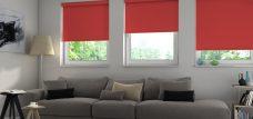 Three Banlight Scarlet Roller Blinds set in a living room