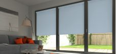 Three Banlight Smokey blue Roller Blinds set in a living room