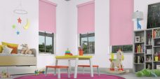 Three Polka Dot Candy Pink Roller Blinds in a child's room