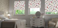 Three Portobello Redcurrant Roller Blinds in a bedroom setting