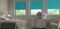 Three Sandbach Aqua Roman Blinds set in recess bedroom windows