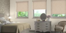 Three Shantung Champagne Roller Blinds set in a bedroom