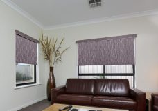 Two lupin-coal-sheer-roller blinds in a lounge