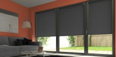 Three Rianna Black Roller blinds set in a conservatory
