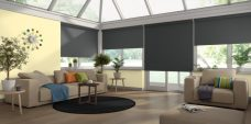 Four Rianna Duo Jet Black Blackout Roller Blinds in a conservatory