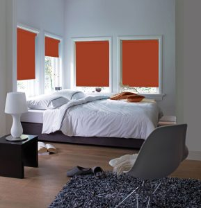 Four Rianna Terracotta Roller Blinds set in a bedroom