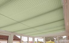 Seven Crush Blossom Solar Reflective Roof Blinds in a conservatory
