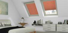 Two Crush Terracotta solar reflective pleated roof blinds in a bedroom