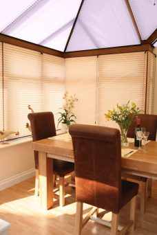 Six Lauren Pale Lilac solar reflective pleated roof blinds in a conservatory