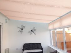 Four Marcello Wheat solar reflective pleated roof blinds in a conservatory